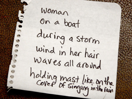 a woman, on a boat, during a storm, wind in her hair, waves all around, holding the mast and singing